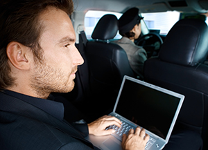 Young man working on laptop computer, sitting in limousine, chauffeur driving.